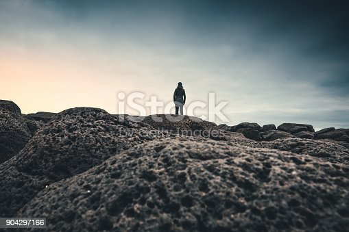 Woman standing on beach in west part of Iceland and enjoying the view.