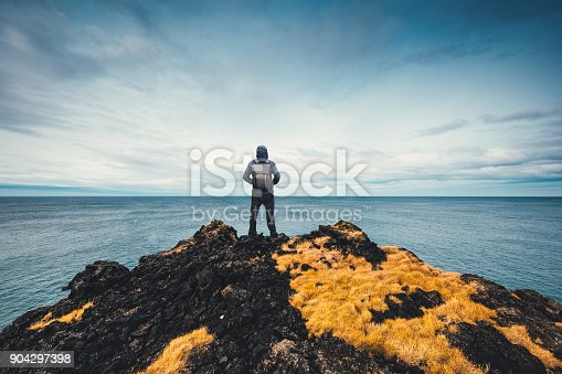 Man standing at the edge of the cliff in Iceland (starring in direction of Greenland).