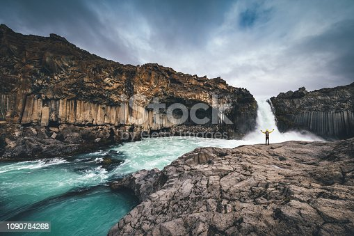 Man exploring Aldeyjarfoss waterfall surroundings in Iceland.