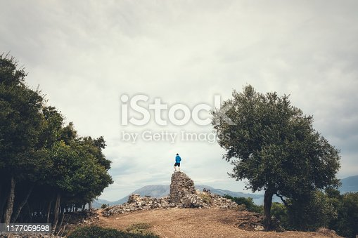 Tourist standing on an old ruin at ancient town Sami, Kefalonia island, Greece.