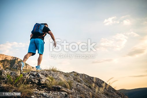Young caucasian muscular handsome man climbing on top of a mountain.