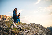 Young Caucasian active heterosexual couple climbing on top of a mountain.