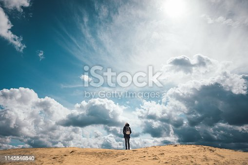 Woman standing on the top of a sand dune (Kale Duinen) in Drents-Friese Wold National Park.