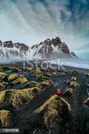 Mature woman standing in a sand dune looking at Stokksnes bay with Vestrahorn mountain in the background.