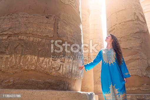 Beautiful caucasian woman enjoying a tour at the Great Temple of Amun in Karnak, Egypt.