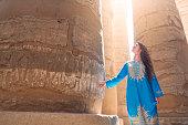 Beautiful caucasian woman enjoying a tour at the Great Temple of Amun in Karnak, Egypt.