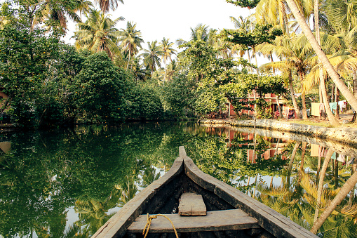 The front of a boat can be seen travelling through the backwaters of Monroe Island in Kollam District, Kerala, South India.