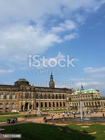Water fountain in a lovely park with people on it in front of historic old buildings in the popular Zwinger in Dresden in Germany May 26,2016