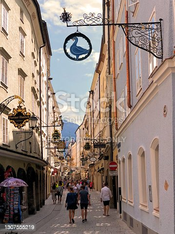 People walking along a small pedestrian way between buildings with shops on a sunny day in the city of Salzburg in Austria June 10,2018