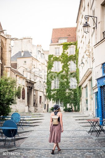 A young woman exploring the empty streets of Paris France in the early morning.