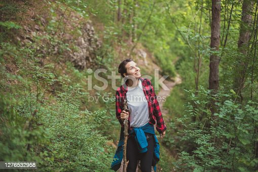 View of a young woman in her outdoor pursuit. She's adventurously overcoming the most difficult parts of the route with a help of a stick, while enjoying beauties of nature all around her.