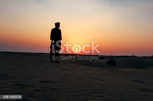 A young man watches the sunset in the Thar Desert, Jaisalmer, Rajasthan, North India.