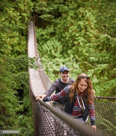 Shot of a young couple walking across a bridge in a natural forest