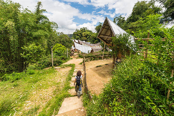 Exploring traditional village in Tana Toraja Backpacker visiting traditional village with typical boat shaped roofs in Tana Toraja, South Sulawesi, Indonesia. Wide angle shot from above. sulawesi stock pictures, royalty-free photos & images