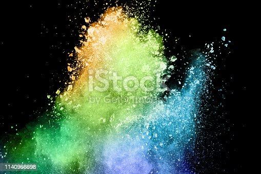 istock Explosion of colorful powder on black background. Splash of color powder dust on dark background. 1140966698