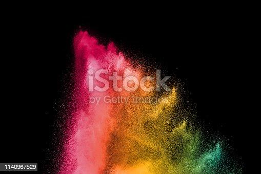 istock Explosion of colorful powder on black background. Splash of color powder dust on dark background. 1140967529