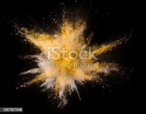 istock Explosion of yellow powder on black background 1057507046