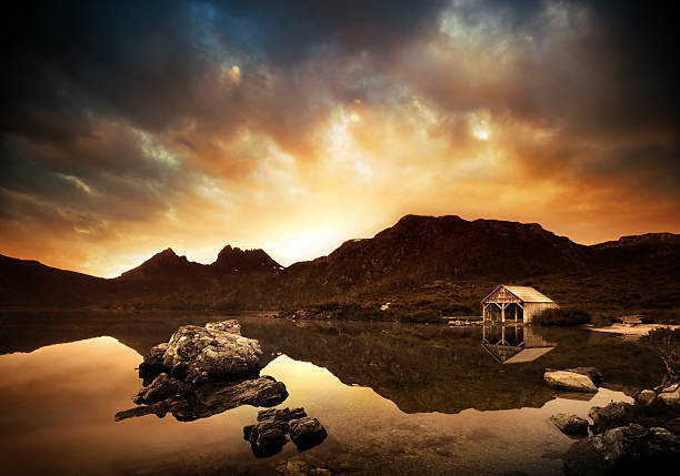 explosive lake sunset - cradle mountain stock photos and pictures