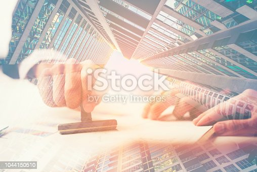 1007078074 istock photo exposure image, A Person's Hand Stamping With Approved Stamp On Document At Desk 1044150510