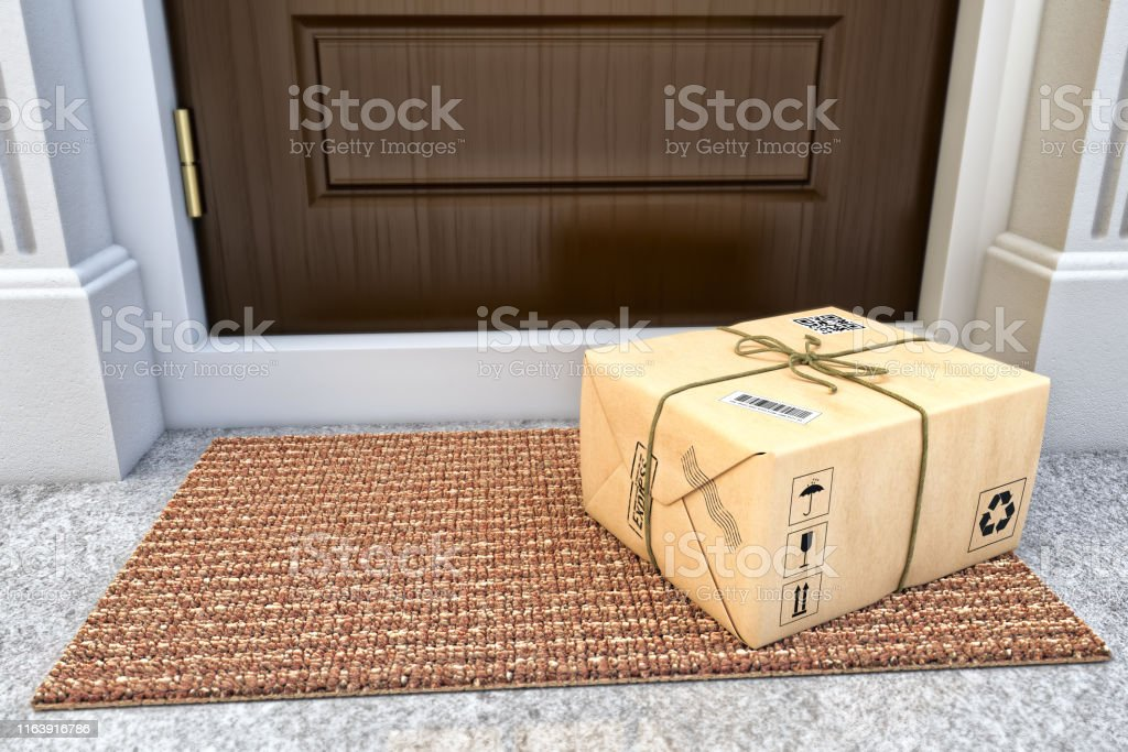Express package delivery service concept Parcel box wrapped in craft paper on the door mat near the entrance door Box - Container Stock Photo