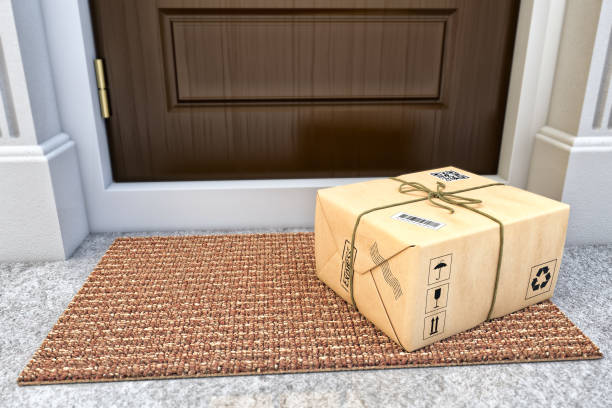 Express package delivery service concept Parcel box wrapped in craft paper on the door mat near the entrance door package stock pictures, royalty-free photos & images