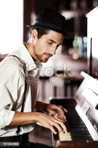 A handsome young man playing the piano in a club