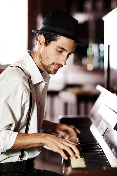 Expressing the music from deep within his soul A handsome young man playing the piano in a club pianist stock pictures, royalty-free photos & images