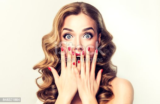 istock Expression of shock on the face of young woman. 848321864