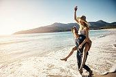 Shot of a young couple enjoying a piggyback ride at the beach