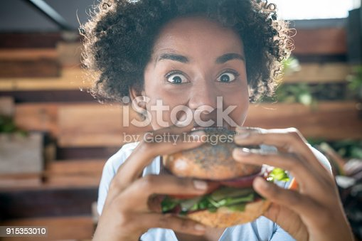 Expressive african american woman eating a delicious vegan burger looking at the camera