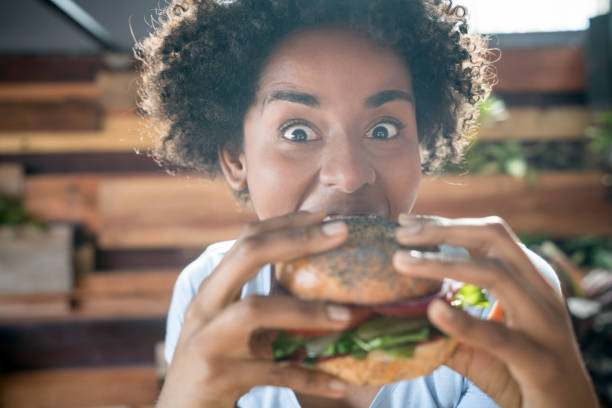 Expressive african american woman eating a delicious vegan burger stock photo