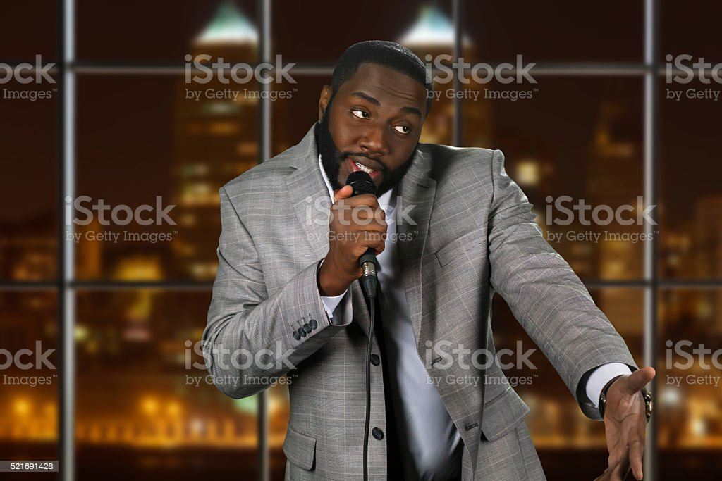 Expressive black man with microphone. stock photo