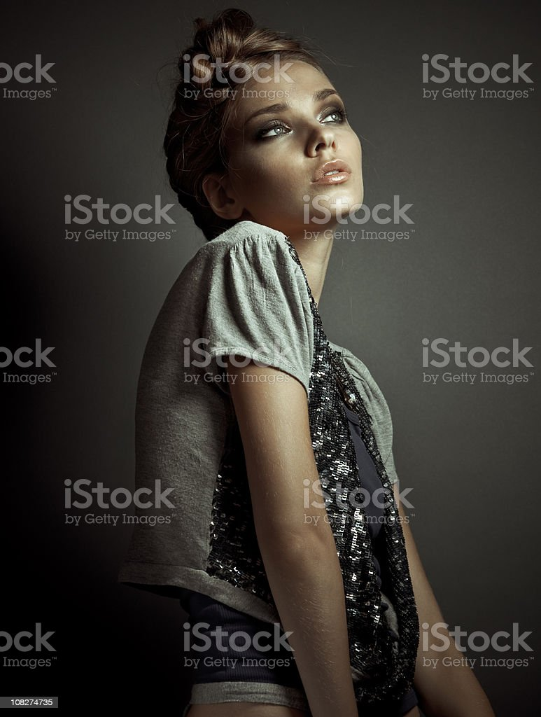 Expressive fashion portrait of young woman on dark background royalty-free stock photo