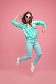 Trendy rebel woman in blue sportive outfit and sunglasses jumping up and screaming on pink background