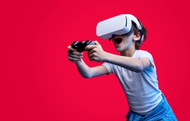expressive kid playing videogame in vr glasses - vr red background imagens e fotografias de stock