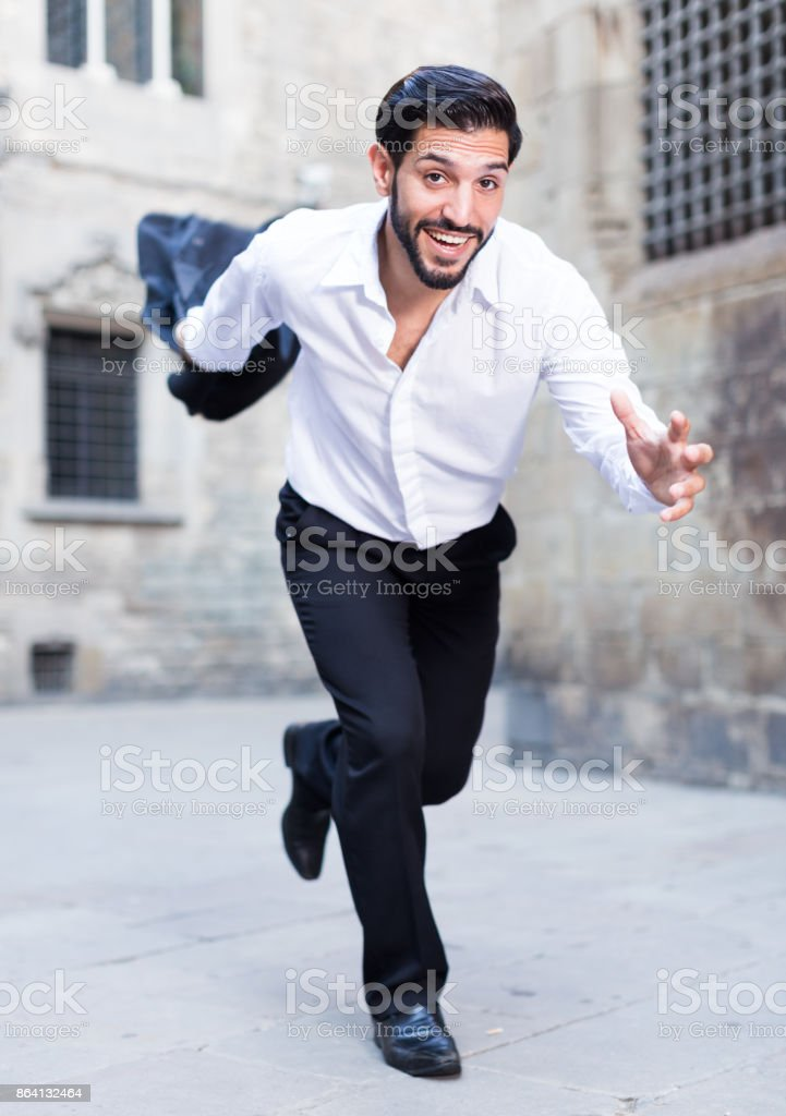 Expressive man running past old city royalty-free stock photo