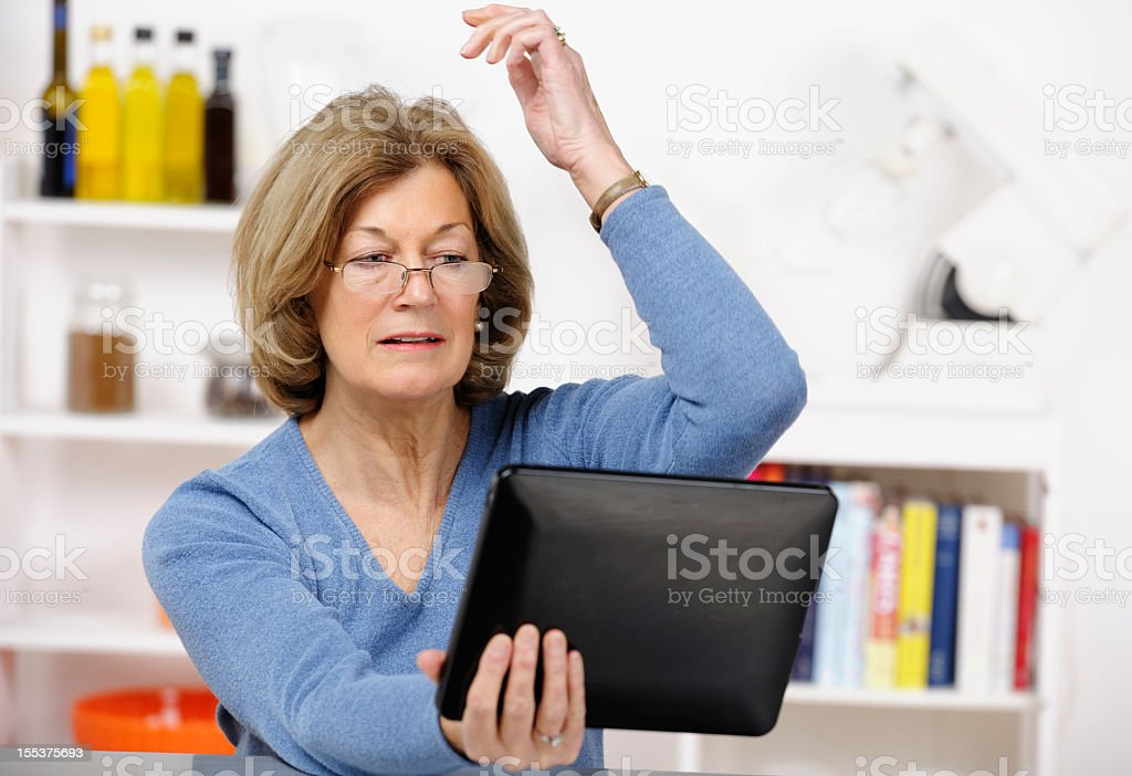Expressive Mature Woman Gambling with Digital Tablet In the Kitchen royalty-free stock photo