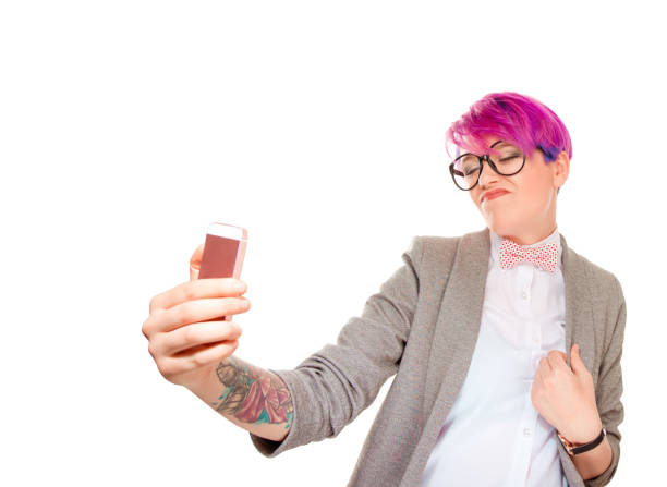 Expressive millennial woman taking selfie Modern woman with short pink hair using phone and taking selfie with grimace of self confidence isolated on white background arrogant stock pictures, royalty-free photos & images