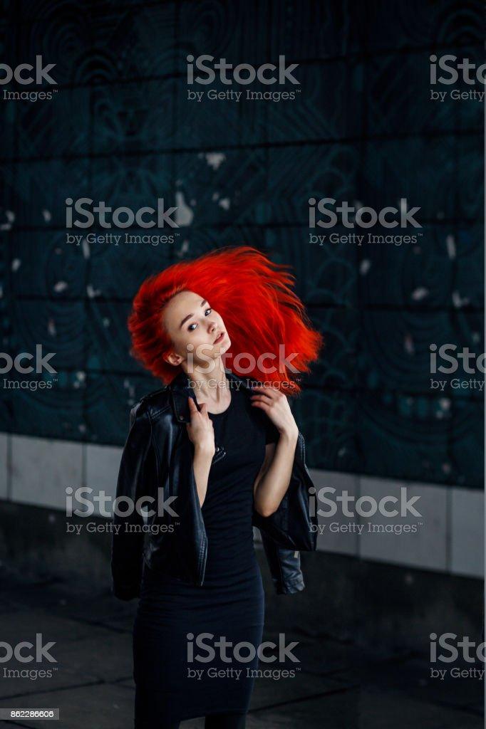 Expressive femme rousse pose au mur foncé et ses cheveux voler sur fond noir - Photo