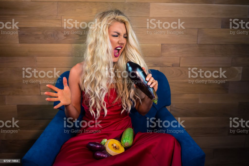 Expressive vegetarian woman sits on armchair on background of wooden...