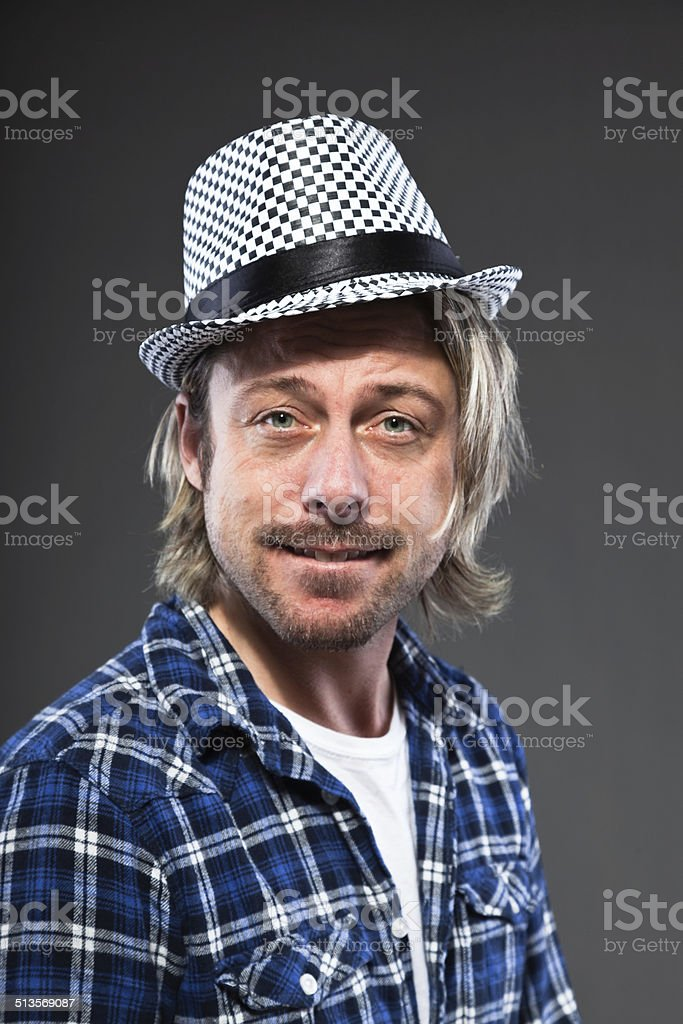 8004a5e18dd Expressive young man with blond long hair and ska hat. - Stock image .