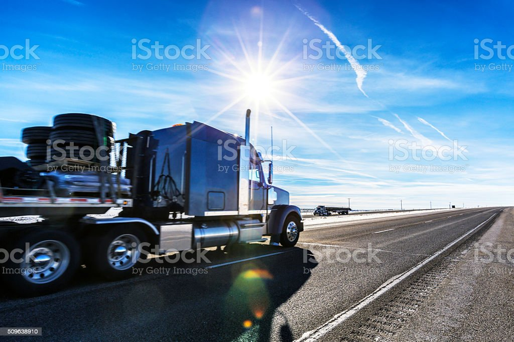 Expressway Flatbed Semi Trailer Trucks on Western USA Sunflare Highway stock photo