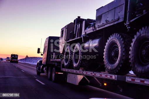istock Expressway Flatbed Semi Truck Convoy Hauling Armored Military Land Vehicles 665295184