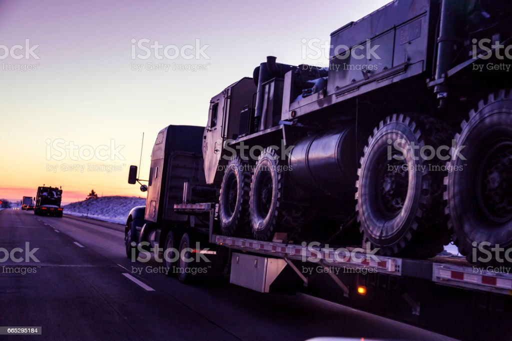 Expressway Flatbed Semi Truck Convoy Hauling Armored Military Land Vehicles stock photo