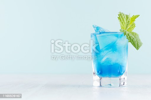 istock Exquisite blue cocktail for celebration in beach style with blue curacao, ice cube, green mint in mint color bar interior on white wood table. 1165526167