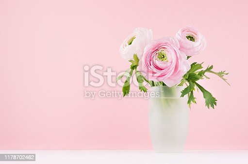 Exquisite pastel pink wedding home decor with sweet roses bouquet in modern transparent vase on soft light white wood table, copy space.