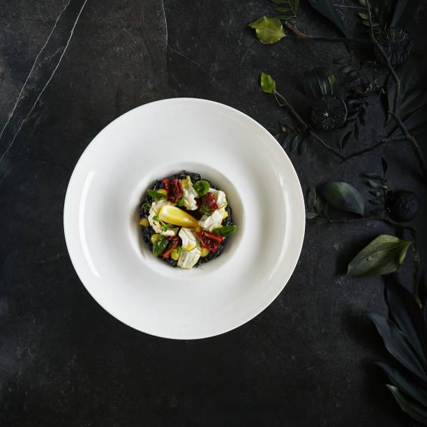 Exquisite Servieren weiß Restaurant Teller mit schwarzem Risotto mit Oktopus, Tintenfisch oder Tintenfisch Fleisch Top View – Foto