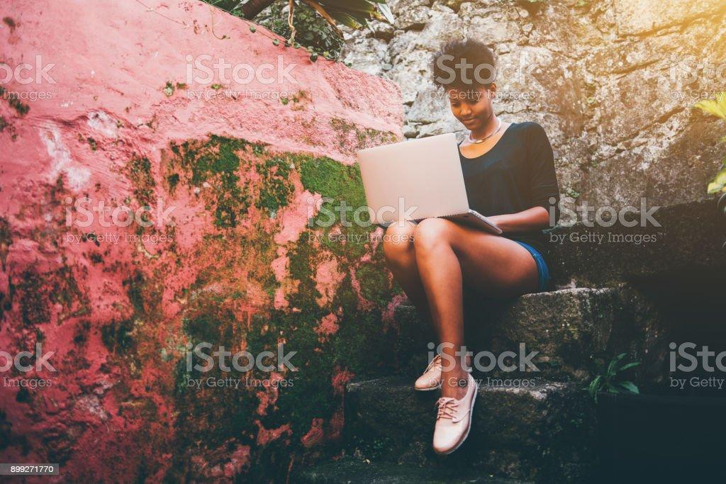 Exquisite junge schwarze Frau mit Netbook auf steinigen Schritt – Foto