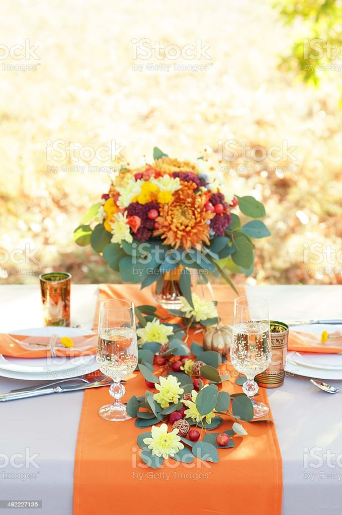 Exquisitely decorated table for two. Autumn themed table setting. stock photo