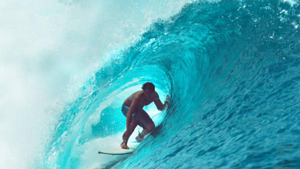 close up: atleta extrema surfea una ola de océano barril grande brilla en el sol. - surf fotografías e imágenes de stock
